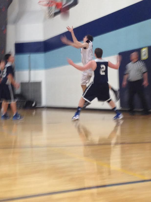 Jack Newman (9th grade), defends the basket as a Maple Grove player drives.